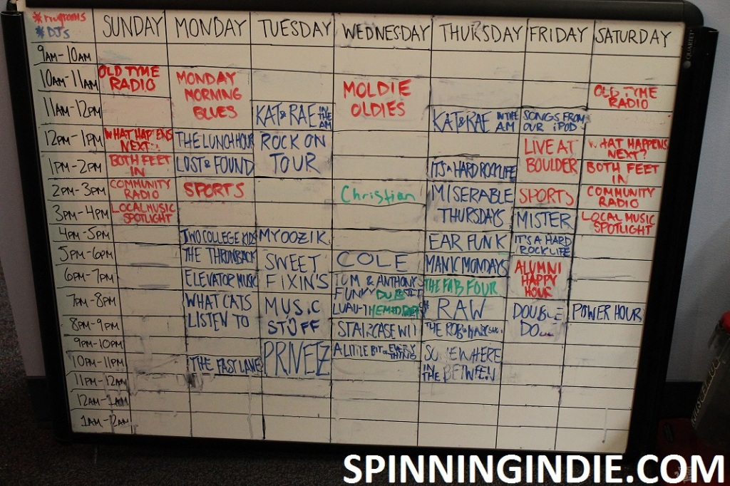 white board with college radio station WLOY's schedule