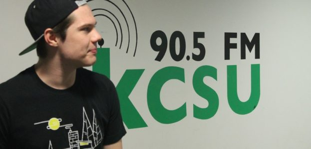 KCSU General Manager Sam Bulkley in front of college radio station's logo. Photo: J. Waits