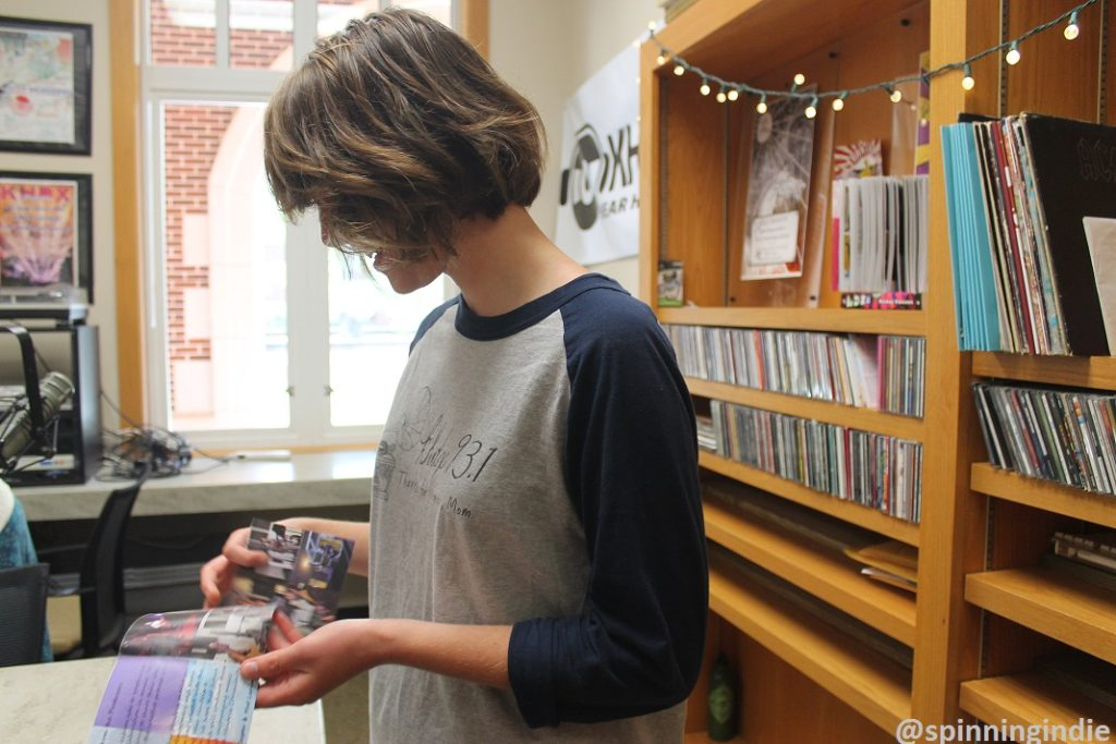 KHDX Station Manager Anna Conard flips through booklet for one of the station's compilation CDs. Photo: J. Waits