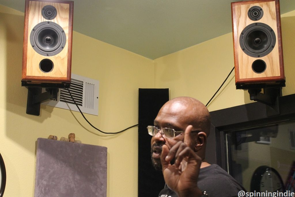 DJ Cat Daddy below the hand-crafted speakers in the KUHS-LP studio. Photo: J. Waits