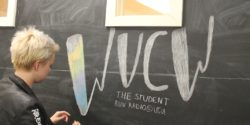 Promotions Director Laura Bryant drawing WVCW on the chalkboard at the college radio station. Photo: J. Waits