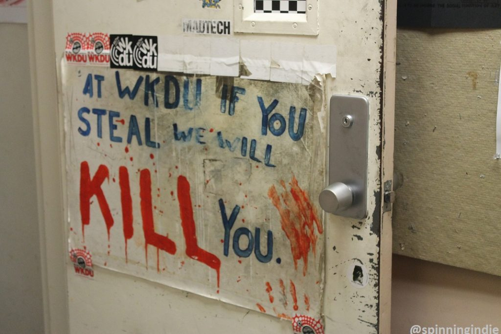 """WKDU if you steal, we will kill you"" sign on the door to the college radio station. Photo: J. Waits"