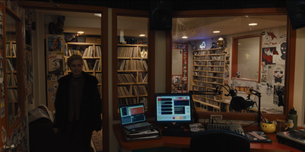 Screen grab from Mare of Easttown. Angourie Rice (as Siobhan Sheehan) enters booth at Haverford College radio station WWXU. We see shelves of vinyl records and CDs in the background. Inside the booth, there is a monitor that appears to be showing an automation program. There's also a laptop on the counter and a small mixing board, with a turntable to the right.