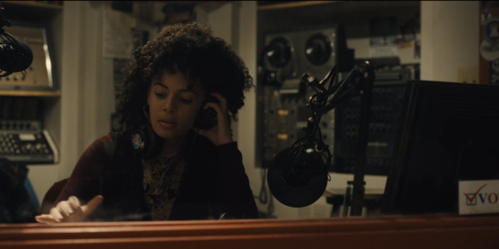 Screen grab from Mare of Easttown. Kiah McKirnan (as DJ Anne Harris) wears headphones in booth of Haverford College radio station WWXU. There's a microphone in front of her and a reel-to-reel machine behind her.