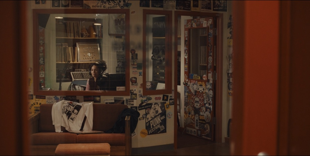 Screen grab from Mare of Easttown. Kiah McKirnan (as Anne Harris) sits in the WWXU booth. The viewer looks in through the window of the station door and we can see a T-shirt flung over an orange couch, sticker and poster-covered walls and door, and audio equipment behind the DJ in the booth.