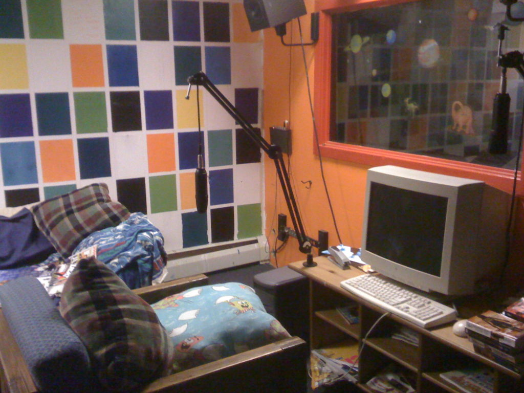 Haverford College radio station WHRC's lounge/live music space with view of Studio B in 2009. Wall with brightly painted squares in the background and an orange-framed window that has planet and dinosaur stickers on it to the right. A table holds a desktop computer and there's a microphone attached to the table with a boom arm. A wood-framed chair has plaid and Sponge Bob pillows and there appears to be a couch behind that. Photo: J. Waits